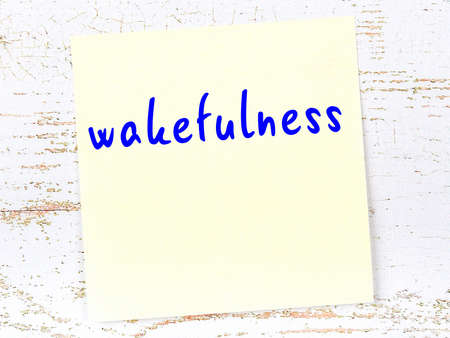 Concept of reminder about wakefulness. Yellow sticky sheet of paper on wooden wall with inscription