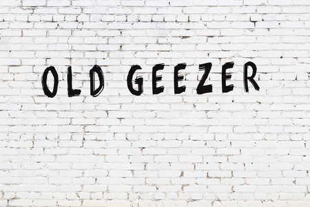 White brick wall with inscription old geezer handwritten with black paint
