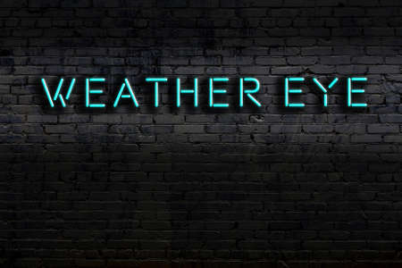 Neon sign with inscription weather eye against brick wall. Night view