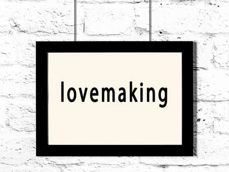 Black wooden frame with inscription lovemaking hanging on white brick wall