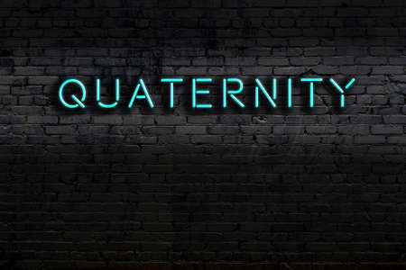 Neon sign on brick wall at night. Inscription quaternity