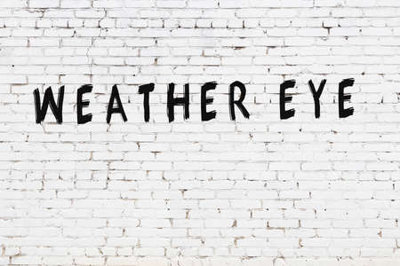 White brick wall with inscription weather eye handwritten with black paint