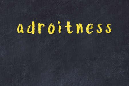 Chalk handwritten inscription adroitness on black desk