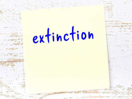 Concept of reminder about extinction. Yellow sticky sheet of paper on wooden wall with inscription