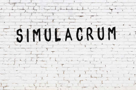 White brick wall with inscription simulacrum handwritten with black paint Foto de archivo