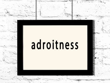 Black wooden frame with inscription adroitness hanging on white brick wall