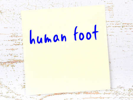 Yellow sticky note on wooden wall with handwritten inscription human foot