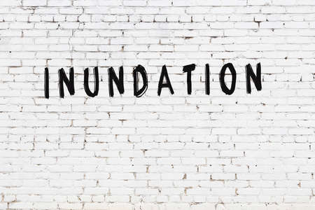 Inscription inundation written with black paint on white brick wall.