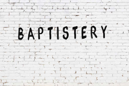 White brick wall with inscription baptistery handwritten with black paint