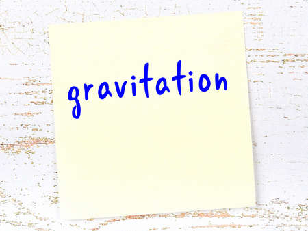 Yellow sticky note on wooden wall with handwritten inscription gravitation