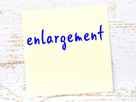 Concept of reminder about enlargement. Yellow sticky sheet of paper on wooden wall with inscription