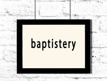 Black wooden frame with inscription baptistery hanging on white brick wall Archivio Fotografico