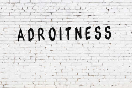 White brick wall with inscription adroitness handwritten with black paint