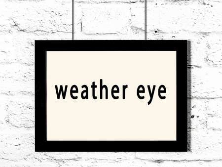 Black wooden frame with inscription weather eye hanging on white brick wall