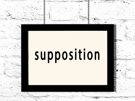 Black wooden frame with inscription supposition hanging on white brick wall