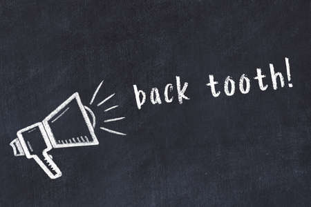 Chalk drawing of loudspeaker and handwritten inscription back tooth on black desk