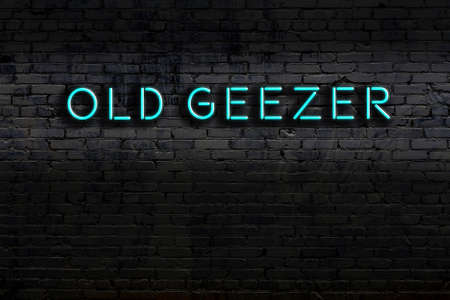 Neon sign on brick wall at night. Inscription old geezer