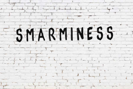 Inscription smarminess written with black paint on white brick wall.