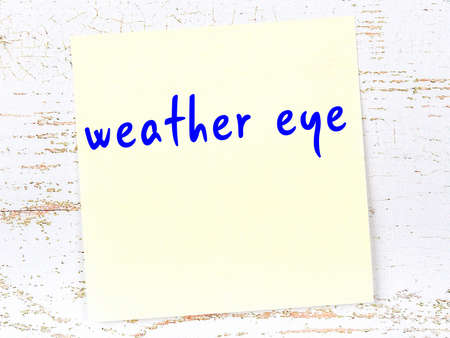 Yellow sticky note on wooden wall with handwritten inscription weather eye