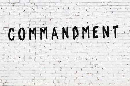 Inscription commandment written with black paint on white brick wall.