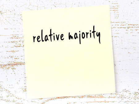 Concept of reminder about relative majority. Yellow sticky sheet of paper on wooden wall with inscription