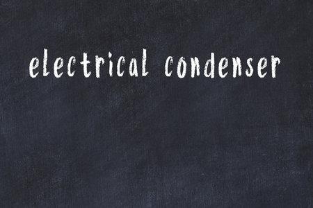 Chalk handwritten inscription electrical condenser on black desk