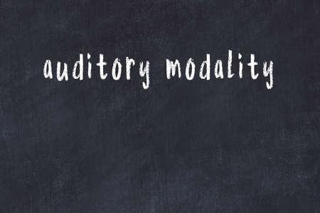 Chalk handwritten inscription auditory modality on black desk