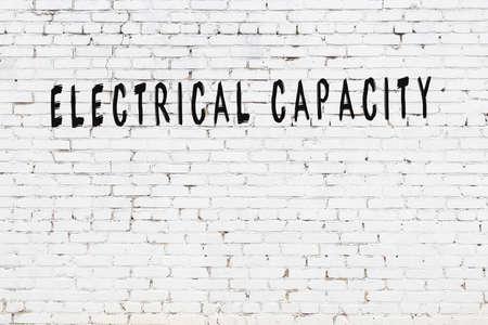 Chalk handwritten inscription electrical capacity on black desk