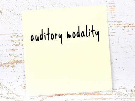 Yellow sticky note on wooden wall with handwritten inscription auditory modality