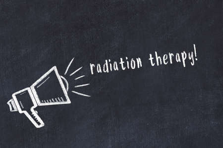 Chalk drawing of loudspeaker and handwritten inscription radiation therapy on black desk