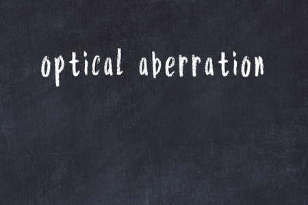 Chalk handwritten inscription optical aberration on black desk