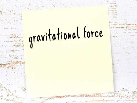 Concept of reminder about gravitational force. Yellow sticky sheet of paper on wooden wall with inscription
