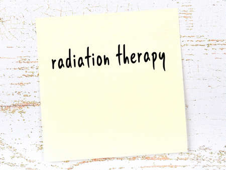 Yellow sticky note on wooden wall with handwritten inscription radiation therapy