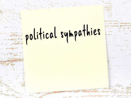 Yellow sticky note on wooden wall with handwritten inscription political sympathies