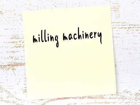 Yellow sticky note on wooden wall with handwritten inscription milling machinery 스톡 콘텐츠