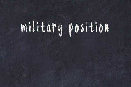 Chalk handwritten inscription military position on black desk