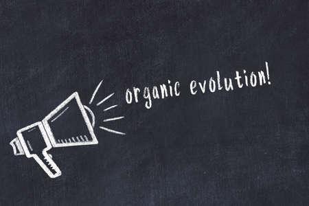 Chalk drawing of loudspeaker and handwritten inscription organic evolution on black desk