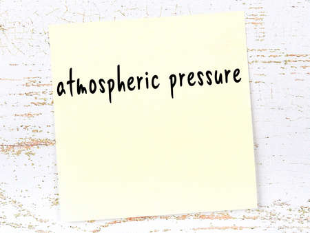 Concept of reminder about atmospheric pressure. Yellow sticky sheet of paper on wooden wall with inscription 스톡 콘텐츠 - 168020002