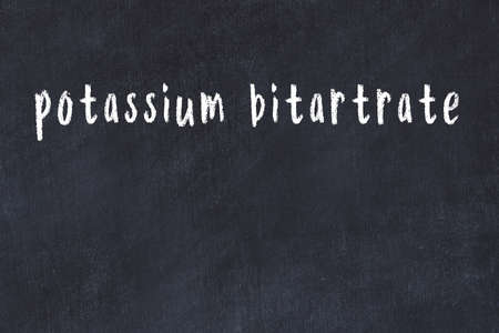 College chalkboard with with handwritten inscription potassium bitartrate on it 스톡 콘텐츠