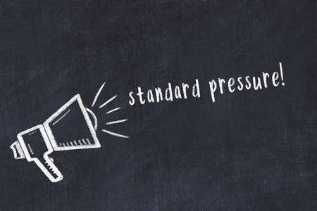 Chalk drawing of loudspeaker and handwritten inscription standard pressure on black desk 스톡 콘텐츠