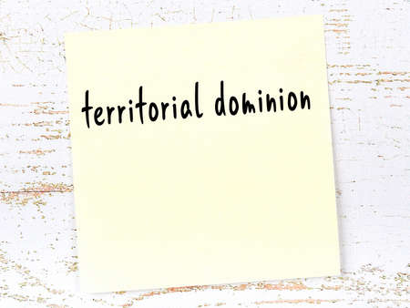 Concept of reminder about territorial dominion. Yellow sticky sheet of paper on wooden wall with inscription