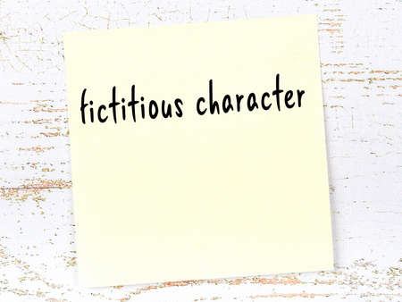 Concept of reminder about fictitious character. Yellow sticky sheet of paper on wooden wall with inscription 스톡 콘텐츠 - 168020051