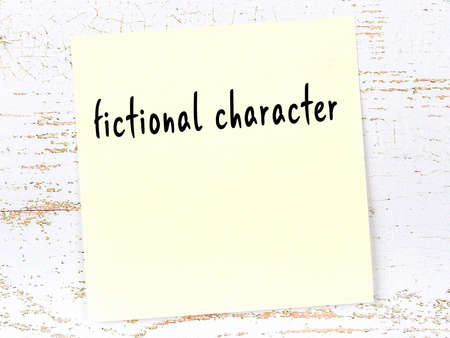 Concept of reminder about fictional character. Yellow sticky sheet of paper on wooden wall with inscription 版權商用圖片