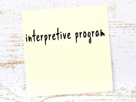 Concept of reminder about interpretive program. Yellow sticky sheet of paper on wooden wall with inscription 版權商用圖片