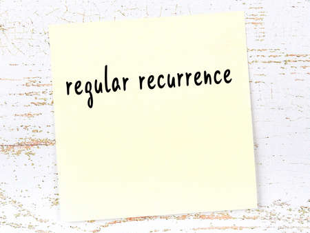 Concept of reminder about regular recurrence. Yellow sticky sheet of paper on wooden wall with inscription 版權商用圖片 - 168020107