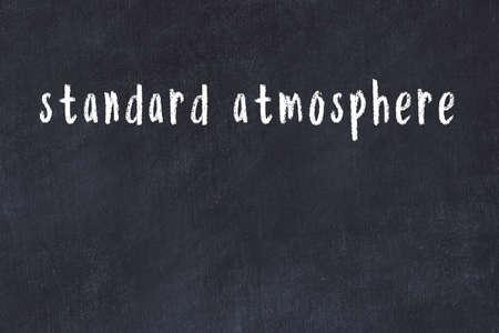 Chalk handwritten inscription standard atmosphere on black desk