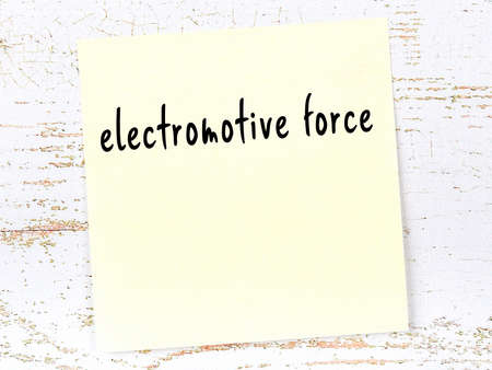 Yellow sticky note on wooden wall with handwritten inscription electromotive force