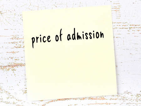 Yellow sticky note on wooden wall with handwritten inscription price of admission