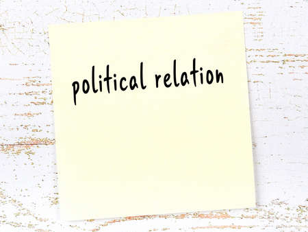 Concept of reminder about political relation. Yellow sticky sheet of paper on wooden wall with inscription 版權商用圖片