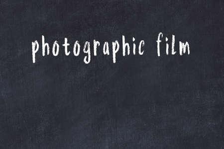 Chalk handwritten inscription photographic film on black desk